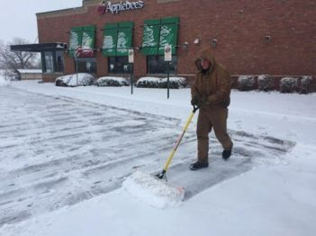 An Applebee's Employee Scooping Snow